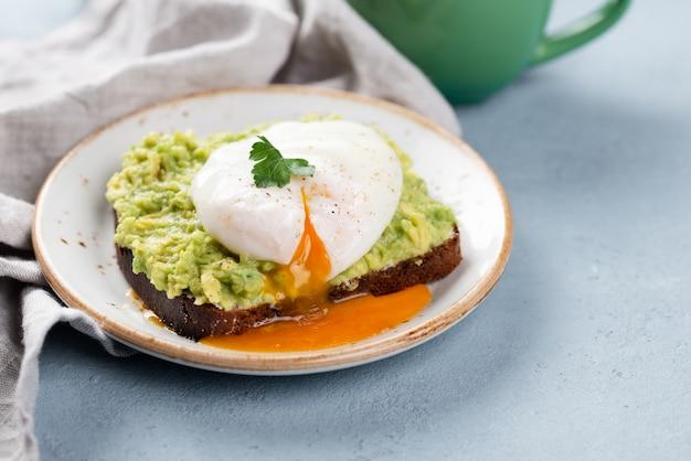 Hoge hoek van avocadotoost met vloeibaar gepocheerd ei bovenop