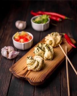 Hoge hoek van aziatisch eten op houten bord met knoflook