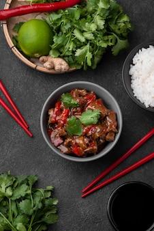 Hoge hoek van aziatische schotel in kom met eetstokjes