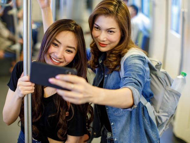 Hoge hoek van aziatische vrouwelijke vrienden die met de trein rijden en zichzelf op een smartphone schieten terwijl ze samen plezier hebben. concept voor het nieuwe moderne reizigers- en stadsleven.