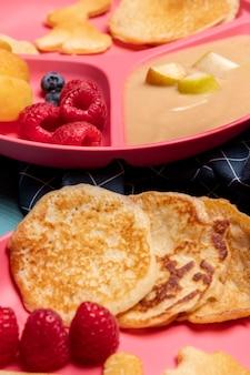 Hoge hoek van babyvoeding met frambozen en pannenkoeken