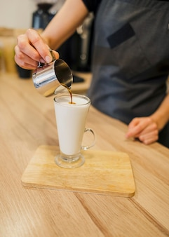 Hoge hoek van barista die koffiedrank maakt
