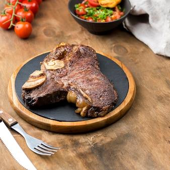 Hoge hoek van biefstuk met bestek en tomaten
