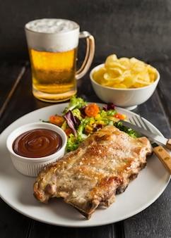 Hoge hoek van biefstuk op plaat met bier en chips