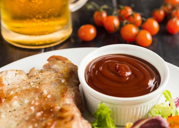 Hoge hoek van biefstuk op plaat met ketchup en bier