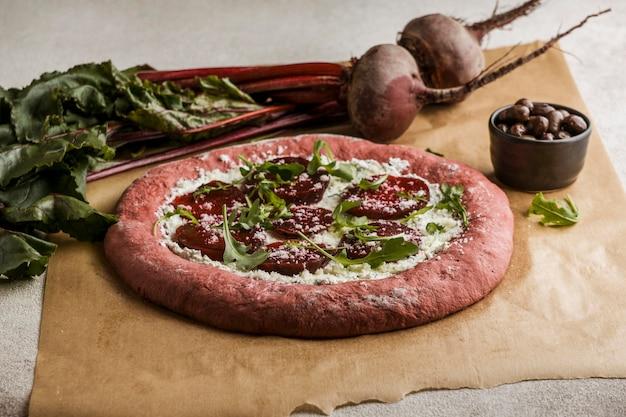 Hoge hoek van bietenplakken op pizzadeeg met kaas