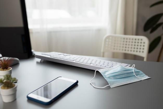 Hoge hoek van bureau met smartphone en medisch masker