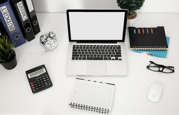Hoge hoek van bureauoppervlak met laptop en notitieboekje