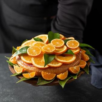 Hoge hoek van cake met stukjes sinaasappel en bladeren