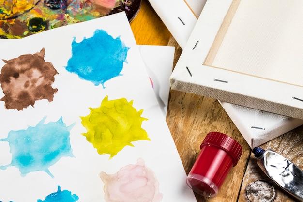 Hoge hoek van canvas en papier met verf