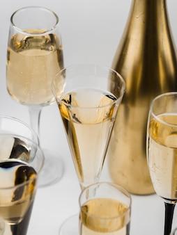 Hoge hoek van champagneglazen en gouden fles