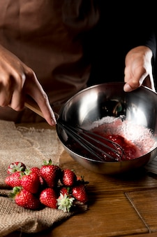 Hoge hoek van chef-kok die aardbeien in kom met suiker zwaaien