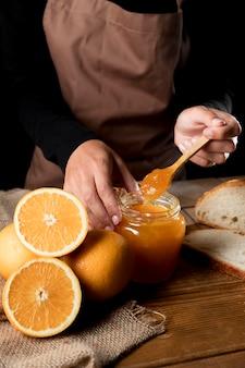 Hoge hoek van chef-kok met pot oranje mnarmalade