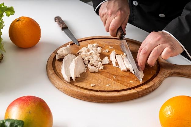 Hoge hoek van chef-kok snijden vlees