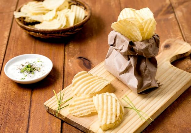 Hoge hoek van chips in papieren zak met saus