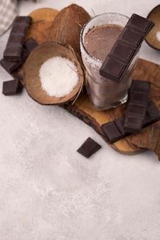 Hoge hoek van chocolade en kokosmilkshakeglas met exemplaarruimte