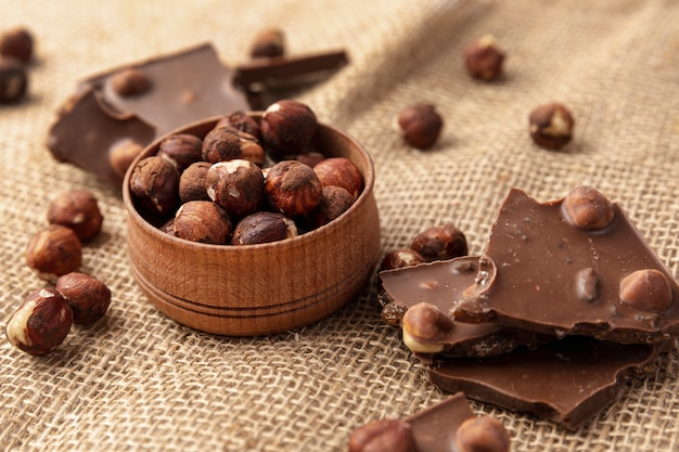Hoge hoek van chocolade met hazelnoten op jute