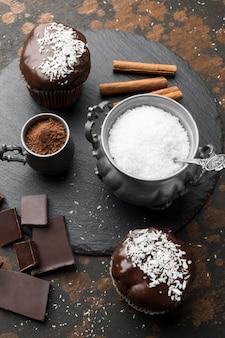 Hoge hoek van chocoladedesserts met kokosvlokken op leisteen