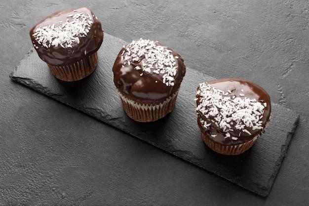 Hoge hoek van chocoladedesserts op leisteen met kokosvlokken