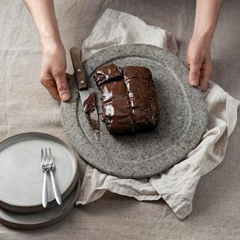 Hoge hoek van chocoladetaart op plaat die door banketbakker wordt gehouden