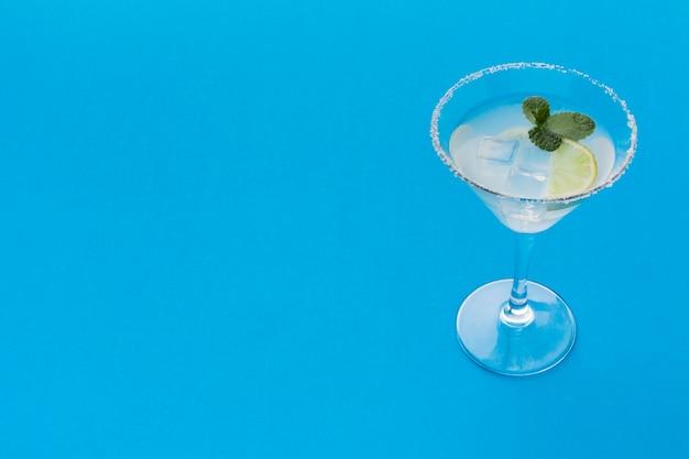 Hoge hoek van cocktailglas met exemplaarruimte en ijsblokjes