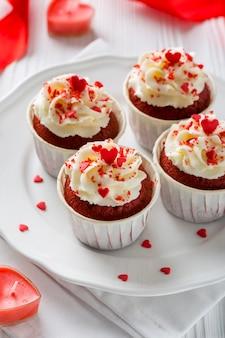 Hoge hoek van cupcakes met glazuur en hartvormige kaarsen