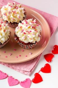 Hoge hoek van cupcakes op plaat met harten