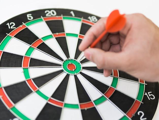 Hoge hoek van dartbord met hand die een pijl aanbrengen