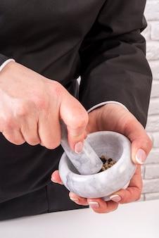 Hoge hoek van de chef-kok met mortier en een stamper