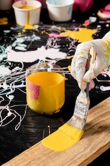 Hoge hoek van de hand met handschoen schilderen met borstel