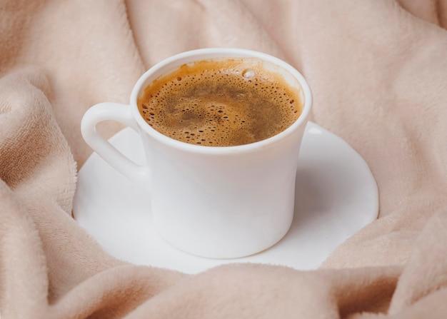 Hoge hoek van de kop van de ochtendkoffie op bed