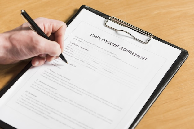 Hoge hoek van de mens die contract voor nieuwe baan ondertekent