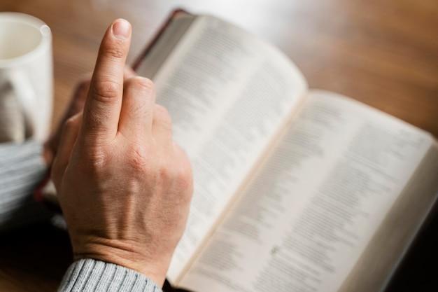 Hoge hoek van de mens die de bijbel leest en vinger wijst
