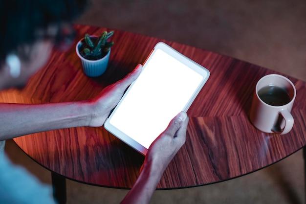 Hoge hoek van de mens die tablet houdt en gebruikt