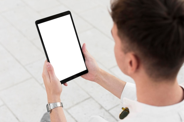 Hoge hoek van de mens die tablet met exemplaarruimte bekijkt