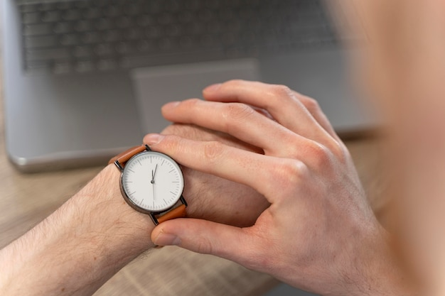 Hoge hoek van de mens die zijn horloge bekijkt