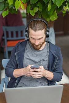 Hoge hoek van de mens op een stadsterras met laptop en smartphone