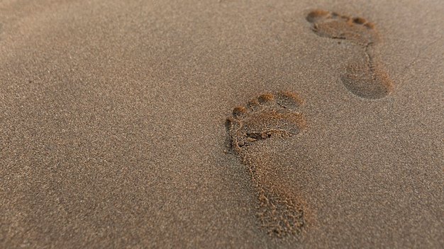 Hoge hoek van de voetafdruk in het zand op het strand