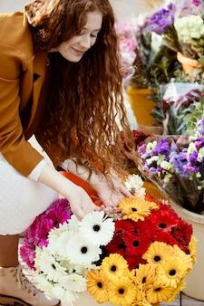 Hoge hoek van de vrouw buiten in het voorjaar met een boeket bloemen
