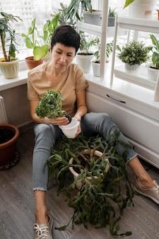Hoge hoek van de vrouw die voor kamerplanten zorgt