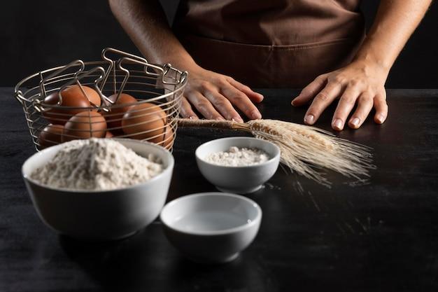 Hoge hoek van deegingrediënten met chef-kok