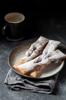 Hoge hoek van desserts bedekt met poedersuiker met koffie