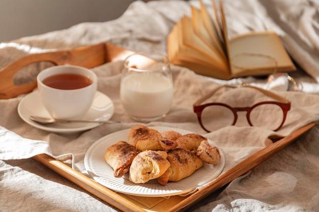 Hoge hoek van desserts op dienblad met glazen en thee