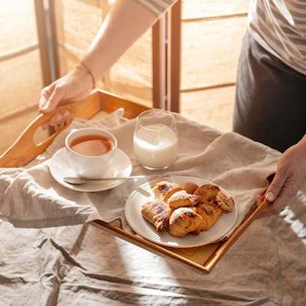 Hoge hoek van desserts op dienblad met melk en thee