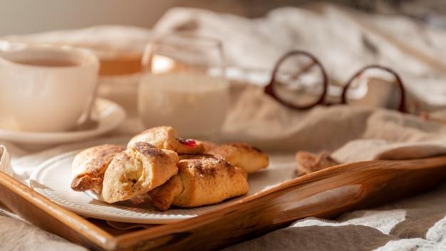 Hoge hoek van desserts op dienblad met thee en glazen
