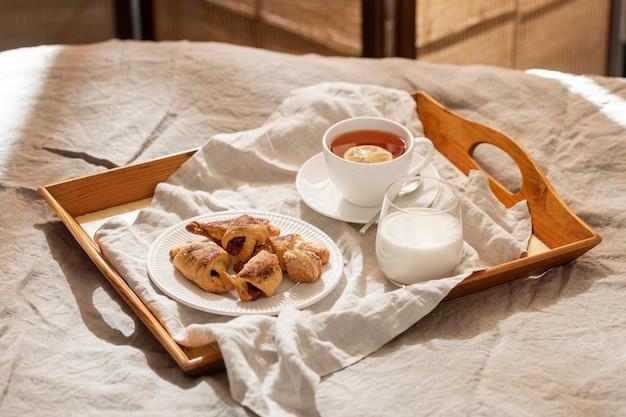 Hoge hoek van desserts op dienblad met thee en melk