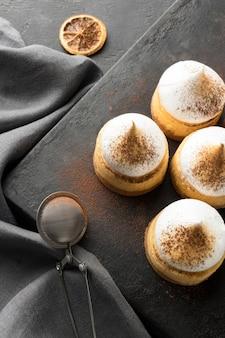 Hoge hoek van desserts op leisteen met cacaopoeder en zeef