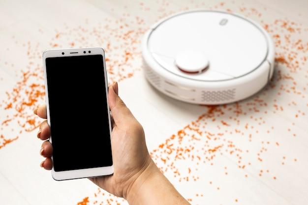 Hoge hoek van draadloos gestuurde stofzuiger met smartphone
