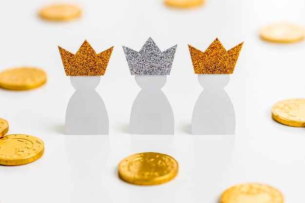 Hoge hoek van drie papieren koningen met munten voor epiphany-dag