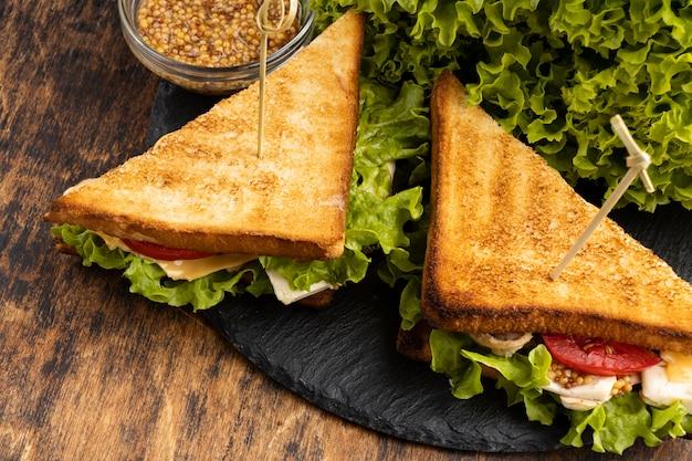Hoge hoek van driehoekige sandwiches op leisteen met salade